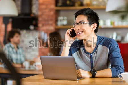Stock photo: Happy  man using laptop and talking on cellphone