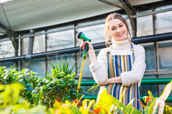 Smiling woman standing in orangery and holding garden hose Stock photo © deandrobot