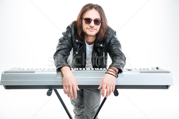 Handsome amusing young man standing and leaning on synthesizer Stock photo © deandrobot