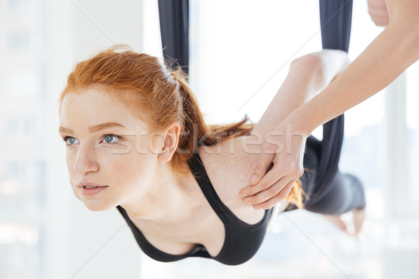 Beautiful woman doing pose of aerial yoga with personal trainer Stock photo © deandrobot