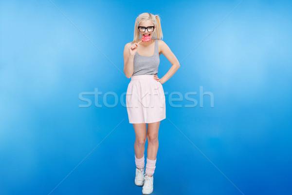 Beautiful young woman eating lollipop Stock photo © deandrobot
