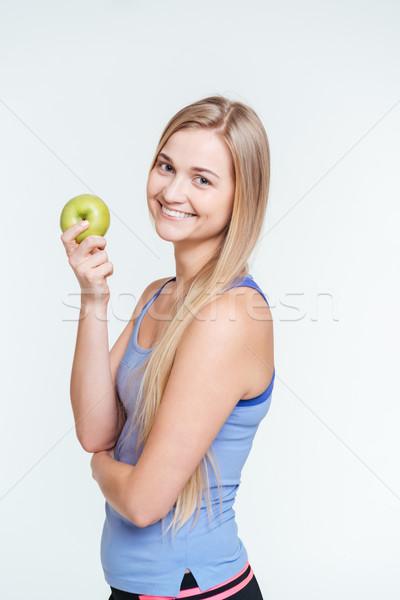 Happy sports woman holding apple Stock photo © deandrobot