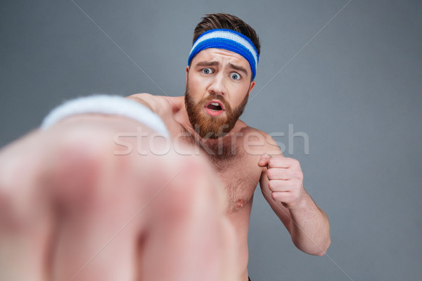 Scared confused bearded sportsman punching at camera Stock photo © deandrobot