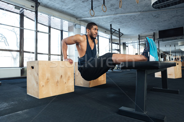Strong fitness man doing muscles exercises in the gym Stock photo © deandrobot