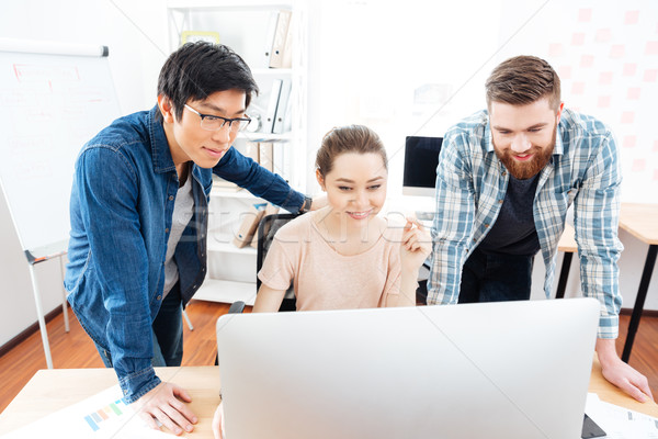 Smiling woman and two men working with computer in office Stock photo © deandrobot