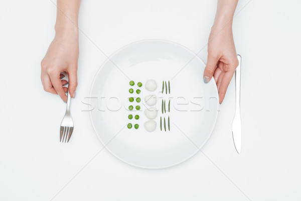 Woman holding fork and plate with green peas, mozzarella, herbs Stock photo © deandrobot