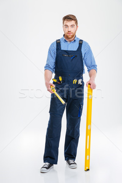 Bearded male builder holding waterpass and measure tape Stock photo © deandrobot