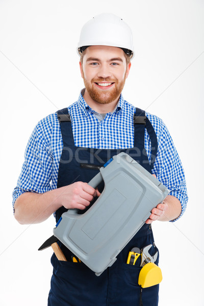 Smiling bearded young worker in helmet holding tool box Stock photo © deandrobot