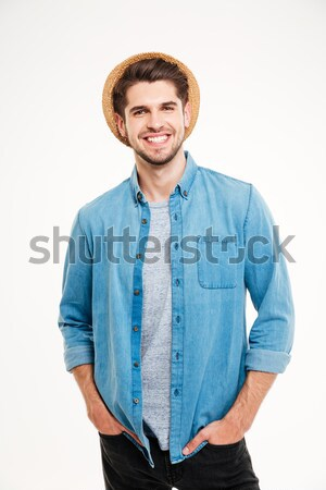 Cheerful young man in hat standing with hands in pockets Stock photo © deandrobot