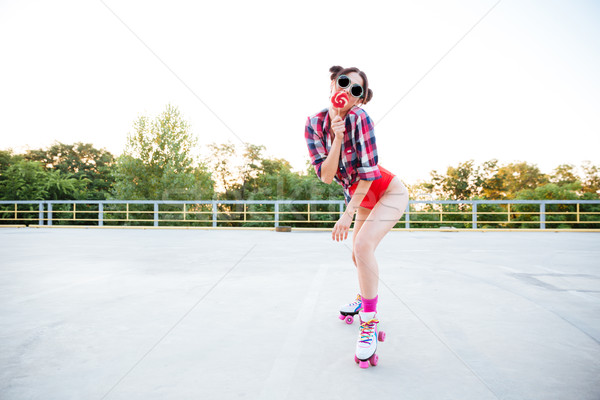 Woman covered mouth with lollipop and standing on roller skates Stock photo © deandrobot