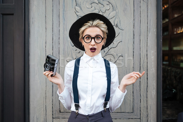 Amazed young woman photographer standing and holding photo camera Stock photo © deandrobot