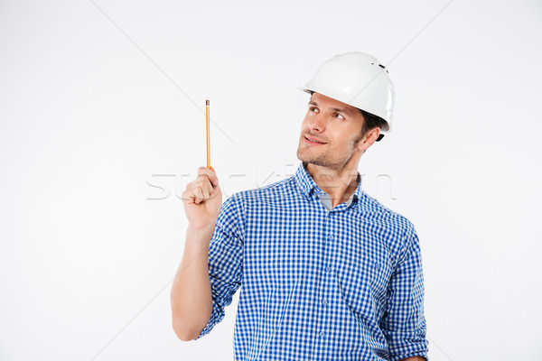 Man building engeneer in hard hat pointing up with pencil Stock photo © deandrobot