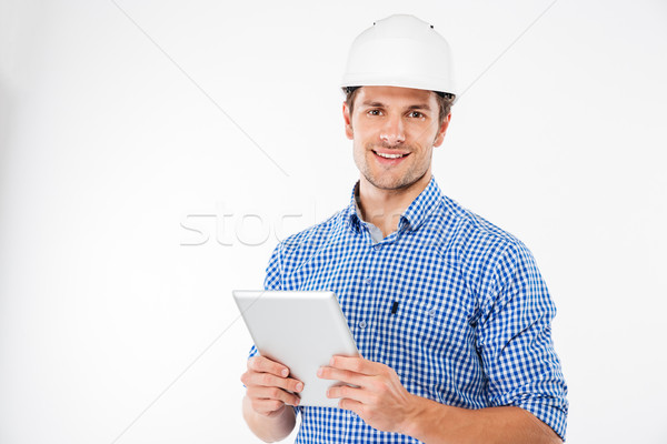 Cheerful man architect in hard hat standing and using tablet Stock photo © deandrobot