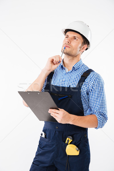 Pensive young builder in helmet thinking and writing on clipboard Stock photo © deandrobot