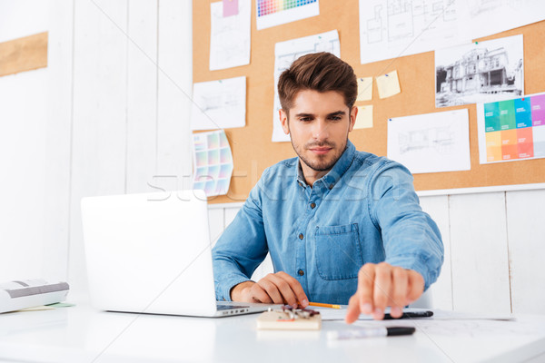 Businessman working with laptop at the office and taking pen Stock photo © deandrobot