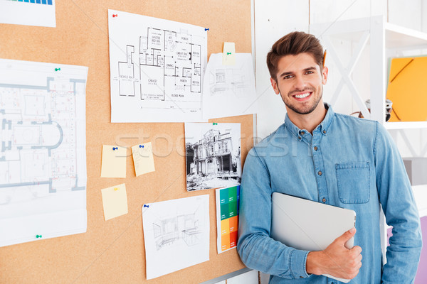 Portrait of a smiling man standing at the task board Stock photo © deandrobot