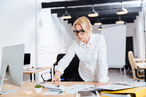 Smiling business woman standing and looking on computer diplay Stock photo © deandrobot