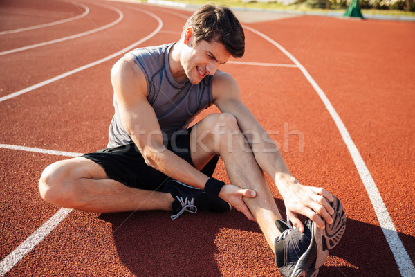 Young male runner suffering from leg cramp on the track Stock photo © deandrobot