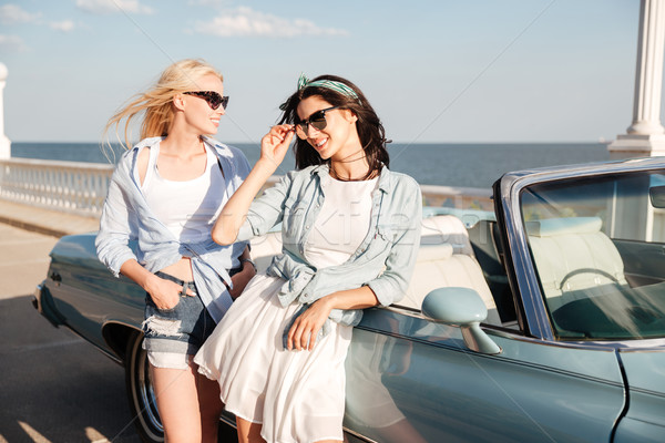 Two beautiful young women standing near cabriolet Stock photo © deandrobot