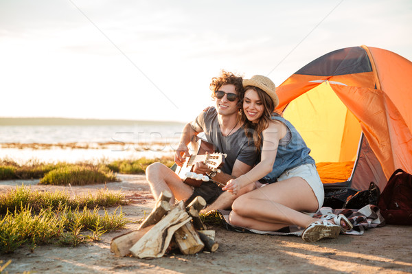 Couple playing guitar and frying marshmallows on bonfire together Stock photo © deandrobot