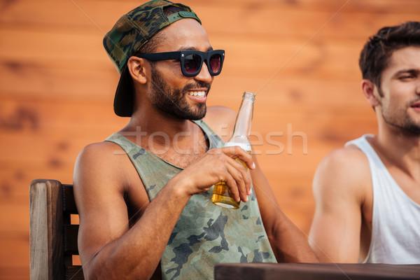 Fiatal afrikai férfi tart sörösüveg szórakozás Stock fotó © deandrobot