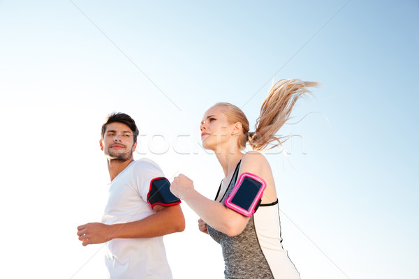 Man and woman joggers exercising outdoors Stock photo © deandrobot