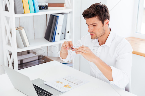 Handsome young businessman taking photo of documents with smartphone Stock photo © deandrobot