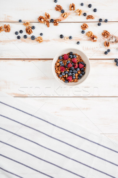 Cereals with berries, nuts and striped napkin on wooden background Stock photo © deandrobot