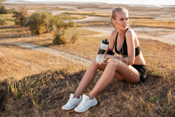 Fitness young woman resting and holding water bottle after jogging Stock photo © deandrobot