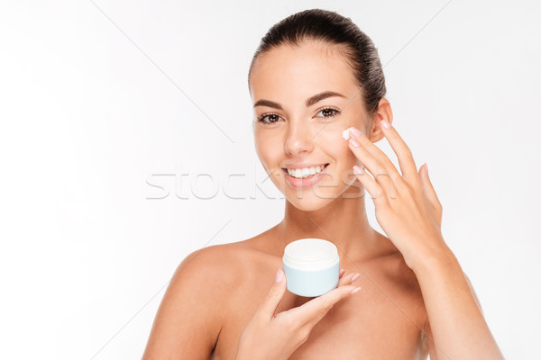 Portrait of young woman applying moisturizer cream on her face Stock photo © deandrobot