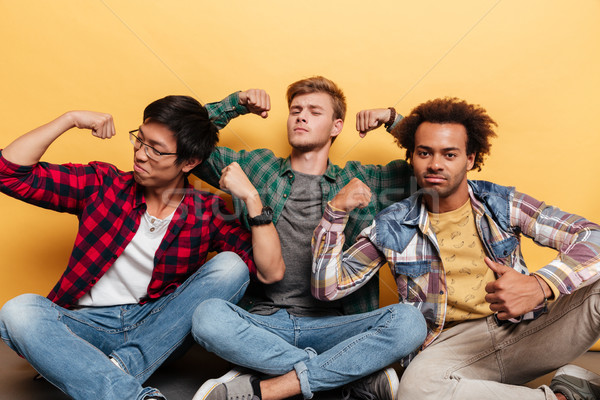 Three amusing young men friends sitting and showing biceps Stock photo © deandrobot