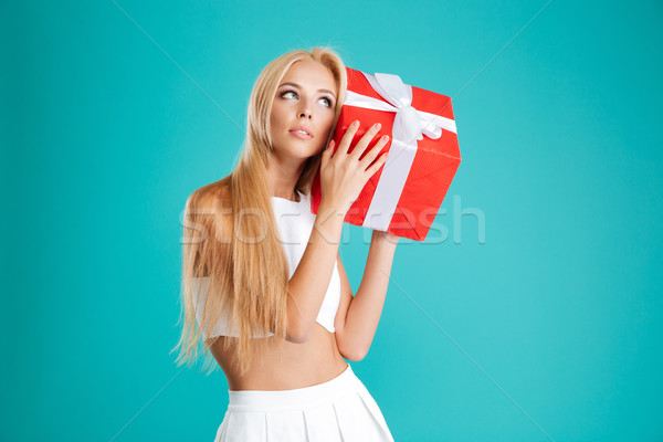Charming wondering woman holding gift box at her ear Stock photo © deandrobot