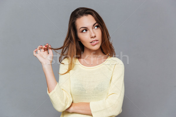 Young pensive woman in sweater looking away and biting lips Stock photo © deandrobot