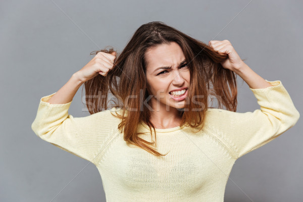 Portrait of a fustrated angry woman pulling her hair out Stock photo © deandrobot