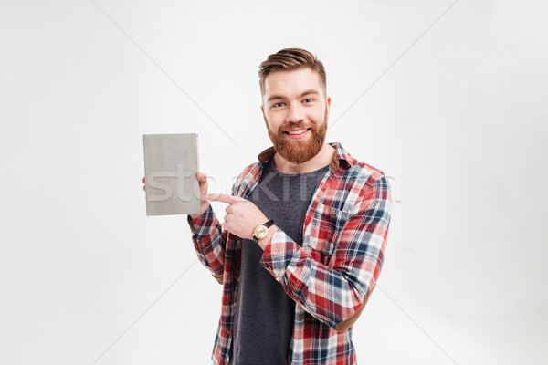 Smiling bearded guy in plaid shirt pointing finger at book Stock photo © deandrobot