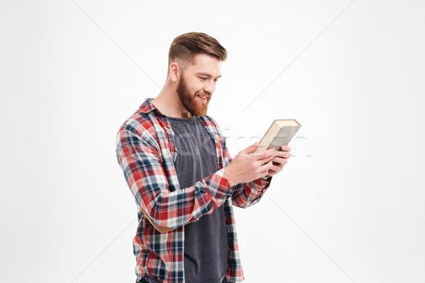 Boldog férfi kockás póló néz könyvborító Stock fotó © deandrobot