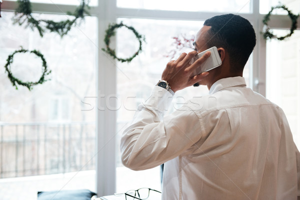 African businessman sitting talking by phone. Stock photo © deandrobot