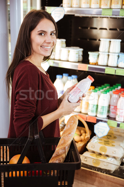 Cheerful young woman with basket on shopping in grocery store Stock photo © deandrobot
