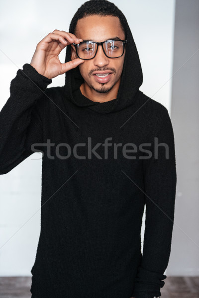 8db31712e00  7846398 Confident african american young man in eyeglasses and black  hoodie by ...