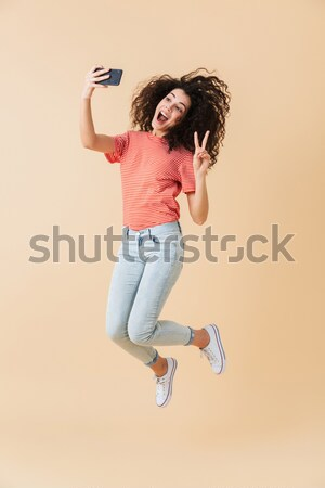 Happy young woman wearing virtual reality device jumping Stock photo © deandrobot