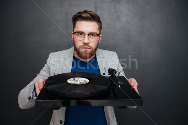 Serious bearded young man in glasses holding turntable Stock photo © deandrobot