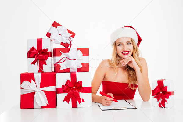 Woman in santa costume with present boxes writing on clipboard Stock photo © deandrobot
