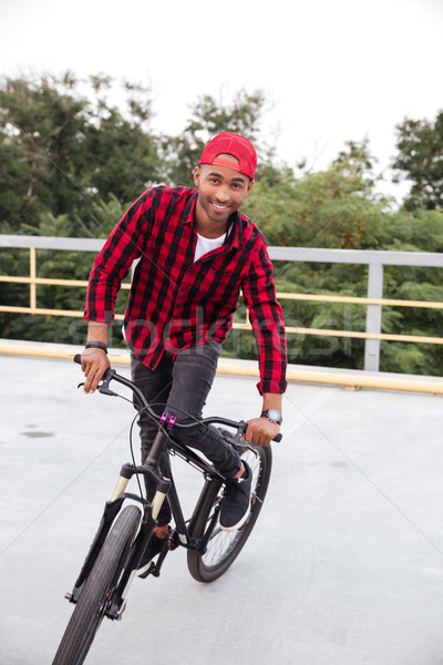 Happy dark skinned man wearing cap sitting on his bicycle Stock photo © deandrobot