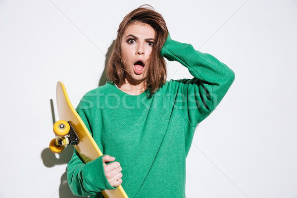 Confused skater lady with skateboard. Stock photo © deandrobot