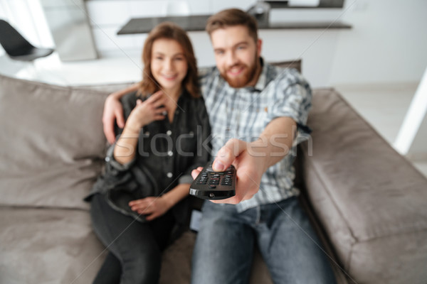 Pretty loving couple sitting on sofa indoors and watching TV. Stock photo © deandrobot