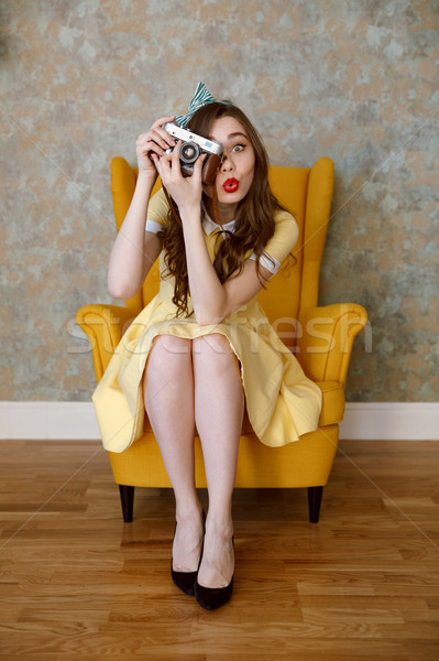 Pretty young pin up woman in dress sitting in chair Stock photo © deandrobot