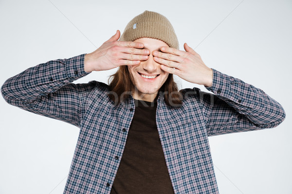 Smiling hipster covering his eye Stock photo © deandrobot