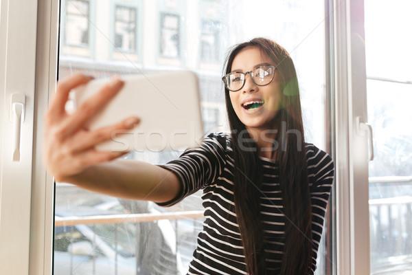Happy Asian woman making selfie on windowsill Stock photo © deandrobot