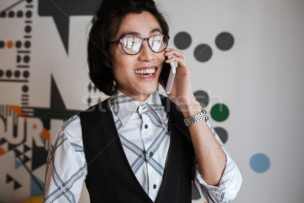 Elképesztő fiatal ázsiai férfi beszél mobiltelefon Stock fotó © deandrobot