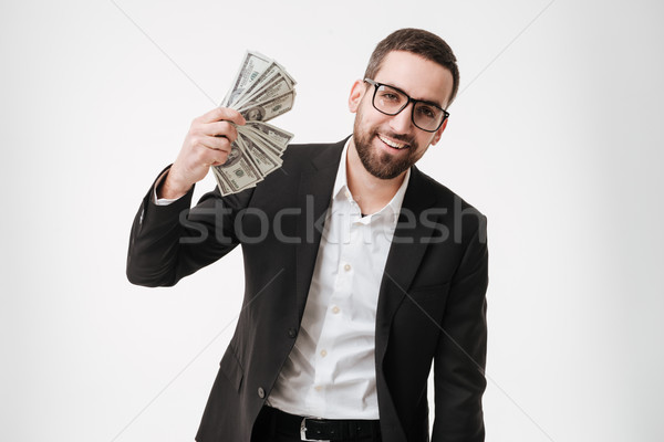 Cheerful young bearded businessman holding money in hands. Stock photo © deandrobot